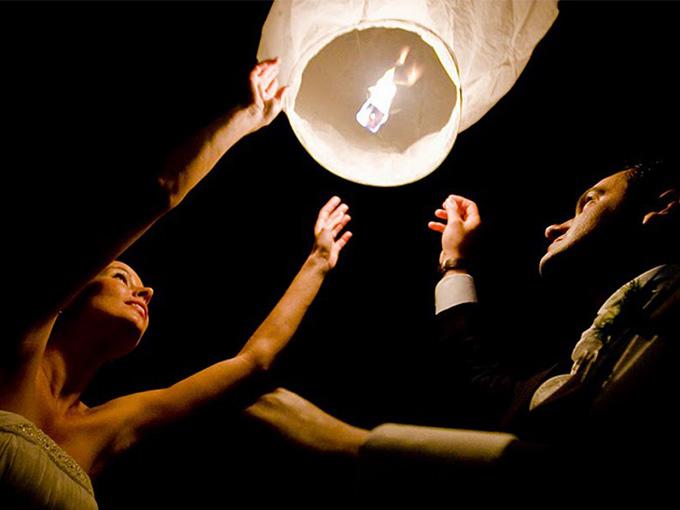 жених и невеста запускают свадебный фонарик